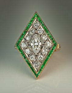 An Art Deco Rhombus Shaped Diamond and Emerald Ring, 1920s. Platinum topped 14K gold ring centered with a prong-set old marquise cut diamond framed by 12 bright white old European and transitional cut diamonds and bordered by numerous channel-set calibre cut emeralds.