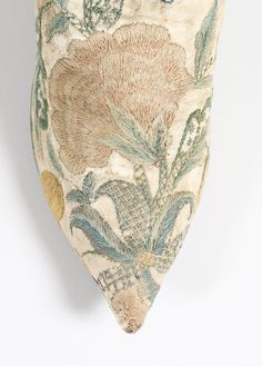 Detail embroidery, pair of lady's shoes, ca. 1720-1730. White kid embroidered in imitation of brocade with large carnations and other blooms, edged in pale blue silk ribbon, straights, with narrow white rand, sharply pointed overhang toe-tip, low curved, heel, lined in linen.