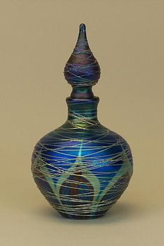 """Peacock  Adorned """"Blue Nouveau Perfume Bottle""""    Art Glass Perfume Bottle    Created byCarl Radke         Dazzling lustrous silver glass threads encircle a delicate feather pattern of rich blues and subtle crimson on this blown glass perfume bottle. Each piece is unique and will vary slightly."""
