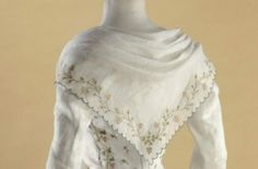 "Detail back view caraco ""pierrot"" style and petticoat, France, c. 1789. White Cotton with mulitcoloured floral embroidery."