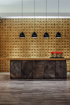 This Spa In China Mixes Traditional And Contemporary Design Elements // The reception area has a large desk, with the stone contrasting the wooden feature wall.