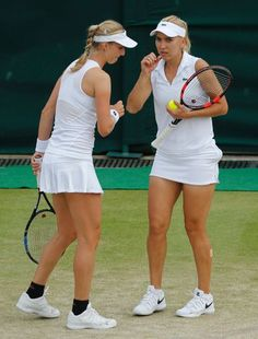 Elena Vesnina of Russia, right, and playing partner Ekaterina Makarova of Russia talk just before serving to Serena Williams of the US, left, and playing partner Venus Williams of the US during their women's doubles tennis match on day eleven of the Wimbledon Tennis Championships in London,Thursday, July 7, 2016. (AP Photo/Ben Curtis)