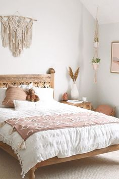boho bedroom wall colors Use a large macrame wall hanging as an over-the-bed statement piece of art. The pink and white color palette in this boho bedroom pair beautifully with the light wood colors. Photo by blakealexiss Boho Bedroom Decor, Wood Bedroom, Room Ideas Bedroom, Bedroom Designs, Boho Room, Bohemian Bedding, Bedroom Inspo, Bedroom With White Walls, Pink And Beige Bedroom