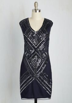 From the Charleston to the foxtrot, this retro, V-neck dress takes your dancing feet where the need to go! This navy sheath stars a glistening, deco-inspired pattern of silver sequins and beads, radiating over your partner as you groove the night away.