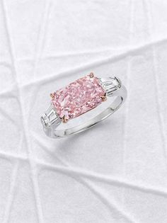 AN EXCEPTIONAL COLORED DIAMOND AND DIAMOND RING. Horizontally-set with a cut-cornered rectangular modified brilliant-cut fancy intense pink diamond, weighing approximately 3.02 carats, flanked on either side by a tapered baguette-cut diamond, ring size 6, mounted in platinum and 18k rose gold.