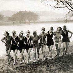 Badpakken. Een rij van negen jongedames poseert in badkleding aan een rivier of meer. Plaats en land onbekend,  1926.