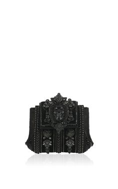 This limited edition structured clutch by **Bea Valdes** features a rich black satin body adorned with black crystals and metal trimmings.