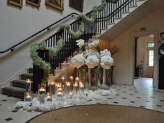 Garland on stair bannister.   Love this idea for  a historic house or hotel wedding ceremony.