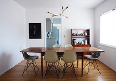 A beautiful farmhouse-like table with Eames chairs.  A perfect combination.