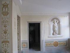 Die Wände sind mehrfach mit einer dünnen Lasur überzogen. der Sockel wurde mit Stucco zum Teil in Gold überzogen. Neben der handgemalten Ornamentik, veredelt diese Illusionsmalerei den Raum.