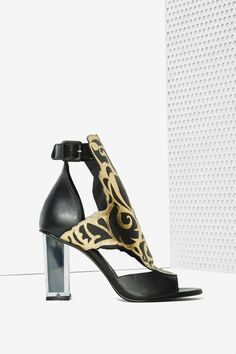 The Rose heel by Miista comes in black leather and features a clear lucite heel with black accent, metallic gold printed upper, open toe, and ankle strap