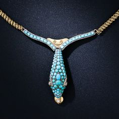 A thoroughly lovely and exotic Victorian-era necklace featuring an exquisitely modeled turquoise serpent centerpiece. The 'V- shape snake, which is holding a diamond heart in its sharp teeth, is composed of pave' turquoise cabochons and sparkling diamond eyes and hangs from an original antique tubular mesh neckchain.