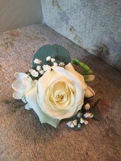 White rose, eucalyptus, gypsophelia and freesia buttonhole