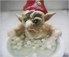 Tiny grumpy elf taking his annual bath in a tiny ceramic mug