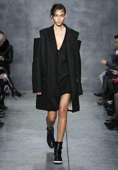 LOOK 2. Black felted wool oversized double-breasted reefer coat with cold shoulder sleeve. Black felted wool V-neck shift dress.