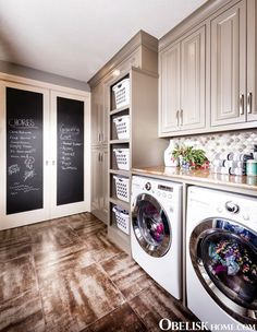 Large laundry room idea with front loading washer and dryer. Chalkboard painted pocket doors are the perfect place to write out chores, shopping lists, and weekly menus.