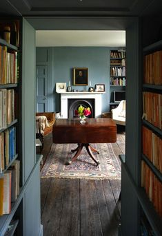 The wall color, the fireplace, drop leaf table, old rug and leather chair, old floor boards, bookcases.