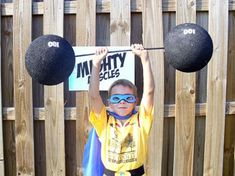 """Take 2 large Styrofoam balls and painted them black, put them on a dow rod - also painted black and used stencils to paint """"100"""" on each to look like it was 200 lbs the kids were lifting. This was a great photo area."""