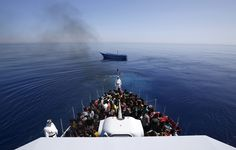 A group of 300 sub-Saharan Africans sit on board the Italian Finance Police vessel Di Bartolo as their boat (center) is left to drift off the coast of Sicily on May 14, 2015. Around 1,100 migrants were rescued off the coast of Sicily, about 130 miles from Lampedusa, according to the police. Alessandro Bianchi / Reuters
