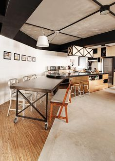This industrial kitchen merges the dining table and kitchen island into one, using the awkward layout of the room to its advantage.