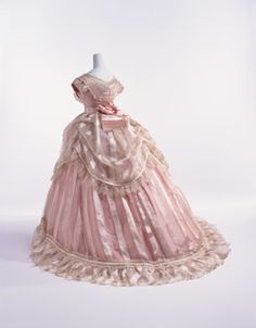 Evening Dress, c. 1866, France. Bodice of sheer ivory striped silk with pink silk taffeta; triple-layered skirt (sheer ivory striped silk skirt and overskirt, and pink silk taffeta underskirt); worn over large crinoline. KCI # AC9380 96-27-1AE. I call this one the puffer-fluffer...