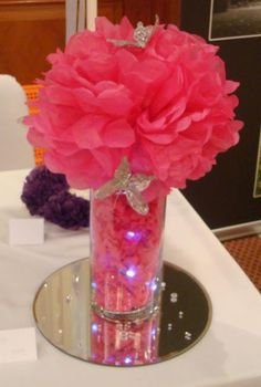 Diy centerpiece...colored shredded paper in dollar store vases, diy tissue balls on top. Butterflies and lights optional