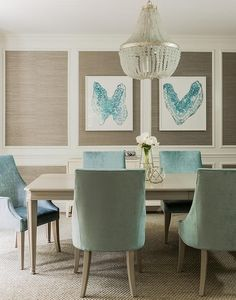 Taupe and turquoise blue dining room features stacked decorative wall moldings filled with taupe grasscloth lined with turquoise blue inkblot style art over a light taupe sideboard cabinet.