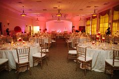 Gold chiavari chairs by A Chair Affair Event Rentals Orlando look perfect at this red and gold themed wedding at Lake Mary Events Center.