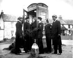 U.S. Coast Guardsmen make use of a telephone booth in Scotland.