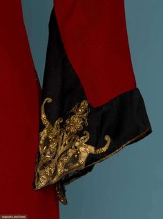 """PAUL POIRET DAY DRESS, 1920s Red wool jersey bias-cut, black silk charmeuse cuffs, hem & yoke outlined in gold braid, beaded gold leather cut-out designs on yoke & cuffs, 5 pair lacing eyelets CF, large """"Paul Poiret a Paris"""" label. Detail"""