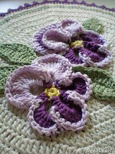 Lovely crochet flower work on the  'Pansy Potholder'  found via Redneval-Lavender