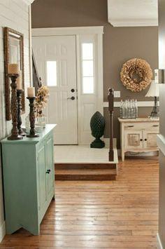 hal d'entrée avec murs de couleur taupe, porte d'entrée en bois blanc, couloir, décoration murale
