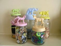mason jars with plastic toy animals glued to the lids and spray painted different colors--cute idea! <3