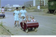 1970 : East Berlin (Lichtenberg)  Gesellig reisen: Während Kindergärten nach dem Zweiten Weltkrieg in der BRD zunächst noch eine eher kleine Rolle spielten, waren in der DDR die meisten Kinder irgendwann in einer Krippe untergebracht. Entsprechendes Fassungsvermögen mussten die dort verwendeten Kinderwagen aufweisen - wie diese Kleingruppentransporter, den Ost-Berliner Krippenarbeiterinnen im Juni 1970 durch Berlin-Lichtenberg schieben.