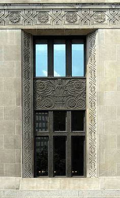 This detail from the Hamilton Post Office, 1929, shows an earlier and more ornate form of Art Deco. The band across the top of the window is a stylized guilloche; the interweaving ribbons become a squared geometric pattern. The central spandrel, like the mullions, is wrought iron with an intricate stylized acanthus in a vase with a flowery background. The mullions are simply geometric patterns.