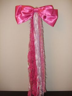 Unicorn tail for UNICORN COSTUME. Make long strands of string, ribbon, fabric, curling ribbon (or your choice of material). Fold them in half to create the length of the tail. Tie a small length of the ribbon in a knot tightly around the middle where you folded. Buy or make the satin bow. Tie bow to middle of tail with the same material. To attack to clothing you can attack a large alligator clip you can buy at a hair supply place like Sally Beauty or you can use a bin back to pin to…