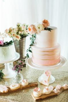 A two-tiered pink-and-gold wedding cake topped with ranunculi and greenery, created by Sugar Suckle.