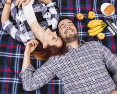 Pareja durmiendo en manta con muchas frutas; hojaldre y botella de champagne Foto gratis