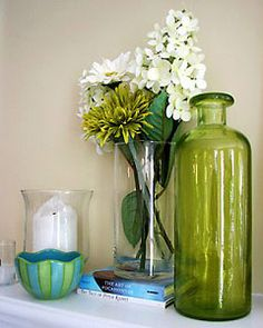 Ornamental Details from The Nest: Artificial flowers are always a nice, lasting alternative to real blooms. Create a bright atmosphere with summer greens and blues. A colored glass vase can make an eye-catching statement even when it's empty.