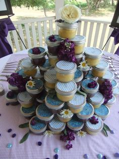 Cake = baked by the bride in each small mason jar. Lemon Cake and Chocolate cake, each lid has a picture and their name, ribbon to match. Stacked like a cake and made to take.