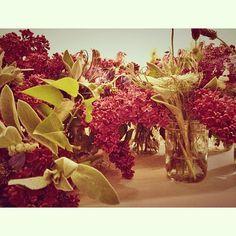 Wild flowers in mason jars as center pieces. Photo by ikthottam