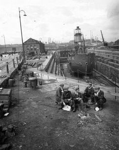 A group of workmen enjoy a lunch break in 1945. Behind them is the North Carr lightship, in dry dock for repairs.