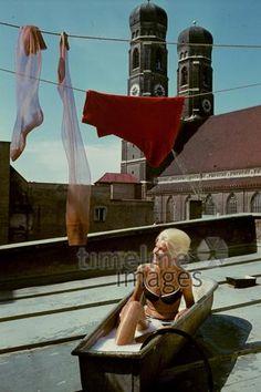 Badende Frau vor Frauenkirche, 1962 Riemer/Timeline Images #60er #60s #1960er #1960s #Badewanne #Wäscheleine #baden #Badehaube #Bikini #Dach