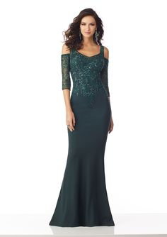 This MGNY by Mori Lee 71828 emerald formal gown features a beaded bodice, with cold-shoulder three-quarter sleeves framing the portrait neckline and mid V-back. This fit and flare dress is crafted in matte scuba, and exits with a sweep train.