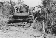 Soviet Union 1941, German soldiers naked, inspect the carcass of a Russian tank KV-1.