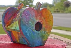 """This birdhouse is called """"The Secrets of Home"""" by artist Lydia Burris.      """"I am inspired by the seemingly random and wild colors and shapes in nature, and choose to infuse my work with intense colors and organic shapes, along with a bit of fantasy and emotion, as seen by the occasional faces peeking out from the work.""""    Find out more at the Partners In Housing website at www.pihdc.org."""