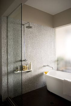 "reminds me of a hotel bathroom (tokyo shangri-la), where the bathtub is part of the ""wet space,"" in addition to the shower. loving the subtle mosaic tiles and unique rubber duckies"