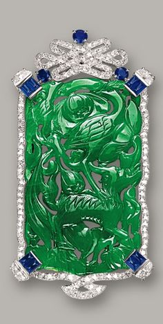 JADEITE, DIAMOND AND SAPPHIRE BROOCH, CARTIER, CIRCA 1950 The jadeite plaque of translucent intense emerald green colour, carved with a crane and mythical beast, symbolising longevity, surmounted by a Chinese eternity knot set with circular-cut diamonds, highlighted by half moon-shaped diamonds, circular-cut sapphires and sugarloaf cabochon sapphires, the diamonds and sapphires together weighing approximately 1.80 and 3.00 carats respectively, mounted