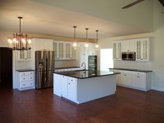 The kitchen of a Musser II-Maple cabinets in Glacier White with Black Absolute Granite countertops (14-89)