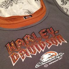 """Screaming Eagle GY OR  Harley-Davidson tank XXL Grey & Orange Two-tone Screamin' Eagle Ribbed Tank Top by Harley-Davidson® features orange Swarovski crystals on front & Screamin' Eagle® logo  Measurements:  armpit to armpit =19"""". Waist left to right=18"""". Hips left to right=23""""  shoulder to hem=25"""". Armpit to hem=16"""". Previously loved. No stains no rips or tears.  Just gently worn. Size XXL Ribbed Cotton Harley-Davidson Tops Tank Tops"""